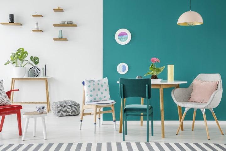 Moderna zelena boja zida sa trpezarijskim stolom i stolicama.